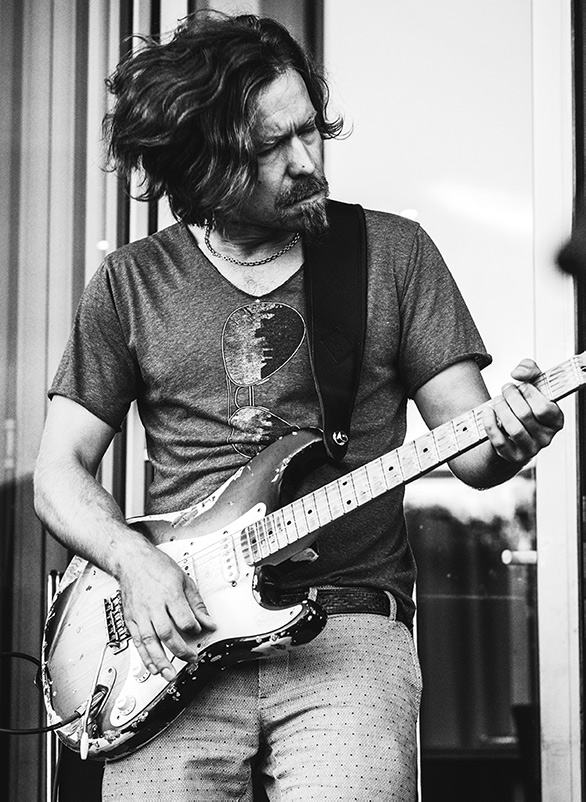 Harri performing with guitar